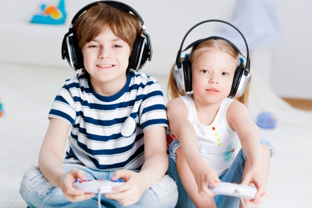 kids playing video games: cute boy and girl playing gaming console in wireless headphones, sitting on the floor