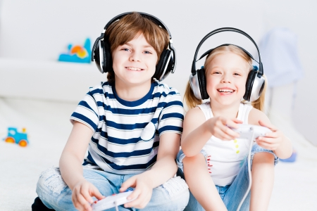 computer game: cute boy and girl playing gaming console in wireless headphones, sitting on the floor