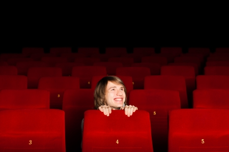 young man in the cinema hiding behind a chair and smiling photo