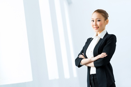 Portrait of a cute asian business woman stands with his arms crossed photo