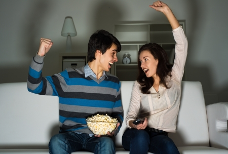 17 20: couple watching TV on the couch, sports fans Stock Photo