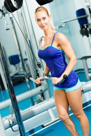 young woman doing body-building in the Gym, live a healthy life photo