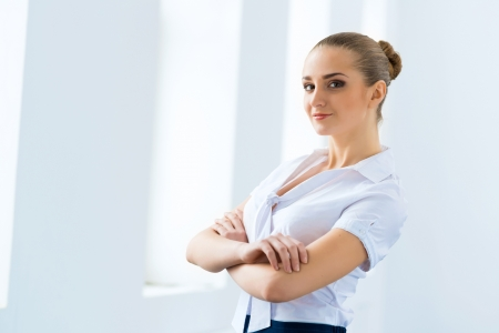 Portrait of a cute business woman stands with his arms crossed photo