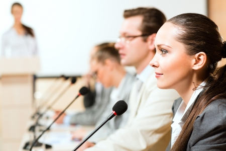 businessmen communicate at the conference, sitting at the table, on the table microphones and documents photo