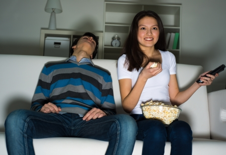 humoristic: woman watching television with enthusiasm, her husband is sleeping next to the couch Stock Photo