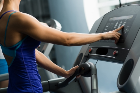 woman adjusts the treadmill at the beginning of training, do fitness in the sport club Stock Photo