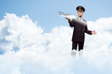 airline uniform: pilot in the form of extending a hand to a flying airplane on the background of sky with clouds