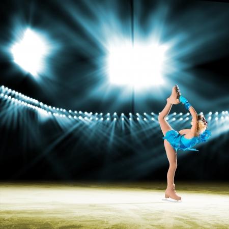performs: giovane pattinatore esegue sul ghiaccio in background illuminazione luci Archivio Fotografico