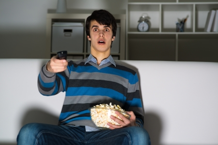 exult: young man watching television with popcorn, remote control switches channels