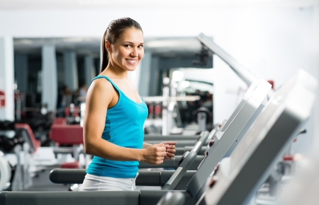 cardio fitness: attractive young woman runs on a treadmill, is engaged in fitness sport club