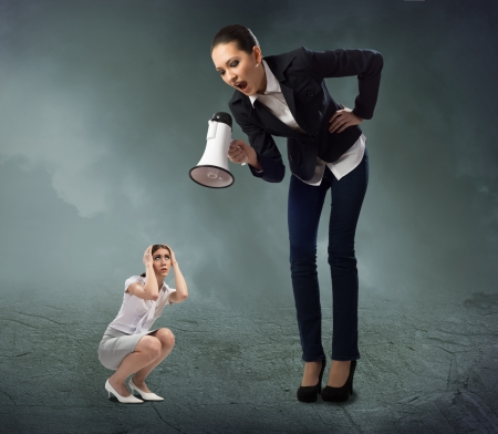 angry boss: Business woman yelling at a small woman sitting on the ground, the concept of aggression Stock Photo