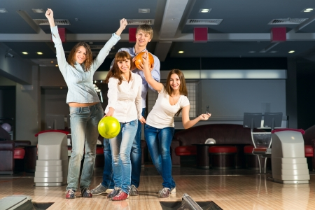 Group of young friends playing bowling, spending time with friends photo