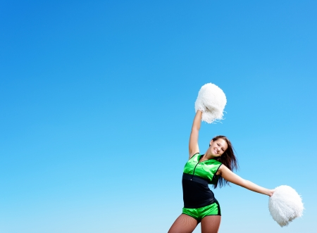 cheerleader girl on a background of blue sky photo