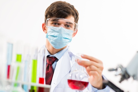 scientist working in the lab, in protective mask, examines a test tube with liquid Stock Photo - 19433200