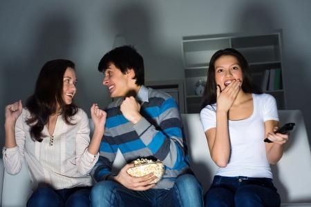people watching tv: grupo de j�venes viendo la televisi�n en el sof�, los aficionados al deporte Foto de archivo