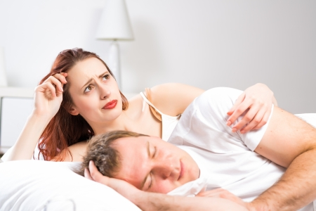 potency: woman sleeping next to her husband in bed, relationship problems people Stock Photo