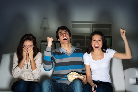 group of young people watching TV on the couch, sports fans photo