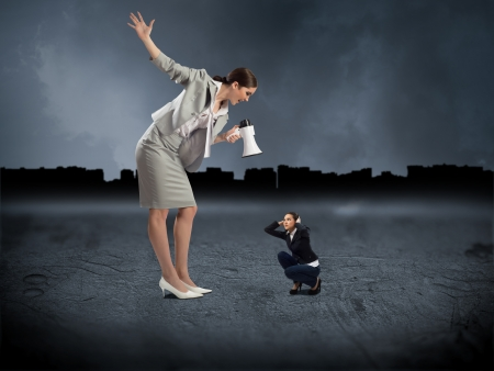 Business woman yelling at a small woman sitting on the ground, the concept of aggression photo