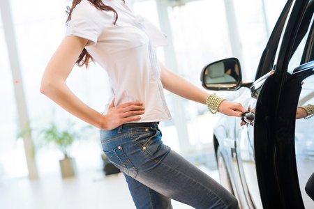 woman opens the door to a new car, car inspection in the showroom photo