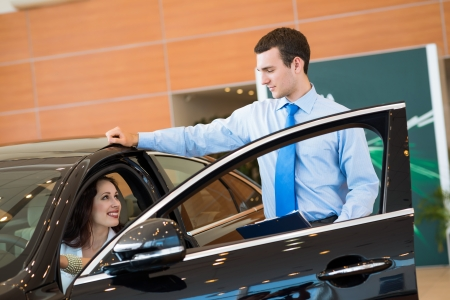 car salesman declares a young girl advantages of the new car photo