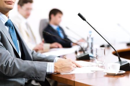 Zakenman schrijven op papier notities, om te communiceren met collega's in de achtergrond Stockfoto