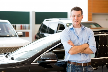 showroom: man standing near a car with his arms crossed, car showroom Stock Photo