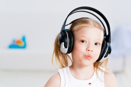 Pretty girl listening to music with headphones lying on the floor in the living room photo