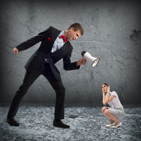 man screams at the frightened woman, the concept of aggression photo