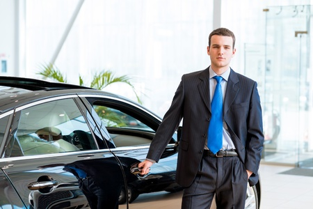 purchasing: dealer stands near a new car in the showroom, put one hand on the car