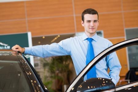 automobile dealers: dealer stands near a new car, car dealerships