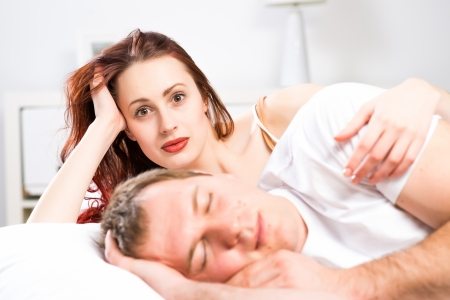 woman sleeping next to her husband in bed, relationship problems people photo