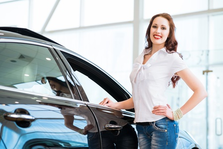 attractive young woman standing near a car in a showroom, chooses a car to buy photo
