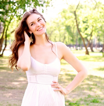 Portret van een aantrekkelijke vrouw in het park, haar haar en lacht Stockfoto