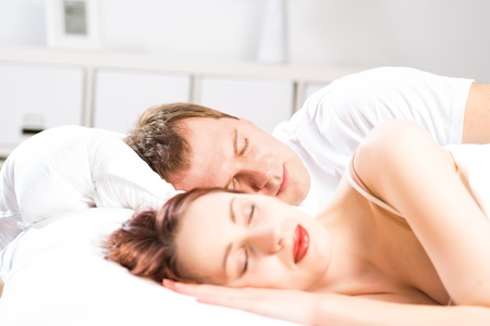 young beautiful woman sleeping on the bed with her husband photo