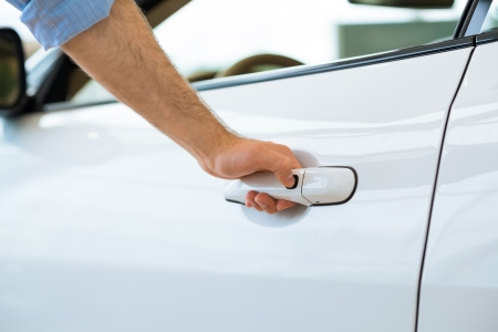 man opens the door to a new car, car inspection in the showroom photo