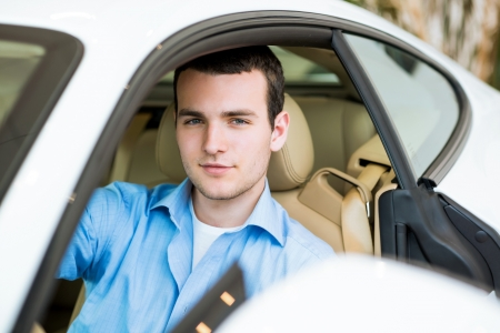 portrait of a man sitting in a sports car in the showroom, make expensive purchases photo