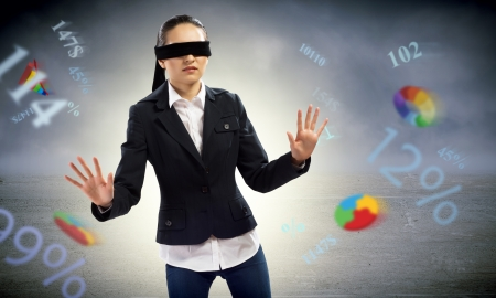 disoriented: young blindfolded woman  can not find a way of flying charts and numbers Stock Photo