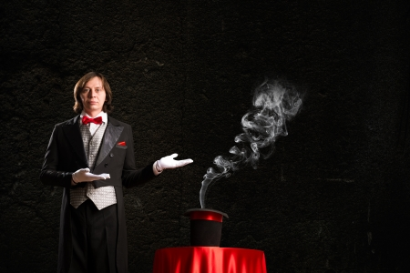 magic young: magician makes passes at the cylinder, the cylinder produces magic Stock Photo