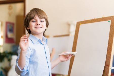 portrait of a boy standing next to his easel, a drawing lesson photo