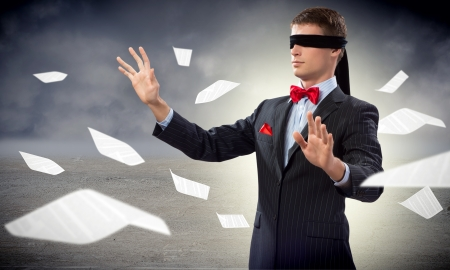 young blindfolded man  his arms and looking for a way out