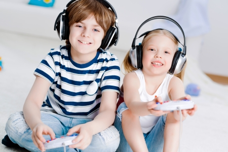 cute boy and girl playing gaming console in wireless headphones, sitting on the floor photo