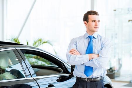 dealer staat dicht bij een nieuwe auto in de showroom, vouwde zijn armen over zijn borst Stockfoto