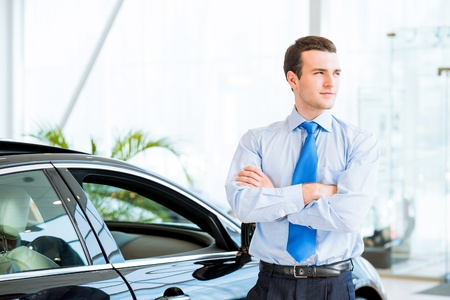 dealer stands near a new car in the showroom, folded his arms across his chest