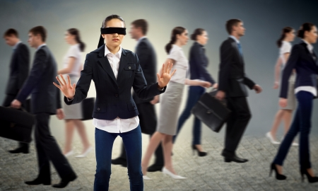hard to find: young blindfolded woman  seeking a way out in a crowd