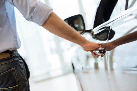 man opens the door to a new car, car inspection in the showroom Stock Photo
