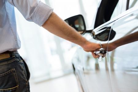 man opent de deur naar een nieuwe auto, autokeuring in de showroom