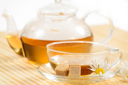 A teacup and a teapot with herbal chamomile tea photo