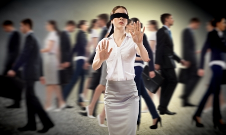 young blindfolded woman  seeking a way out in a crowd photo
