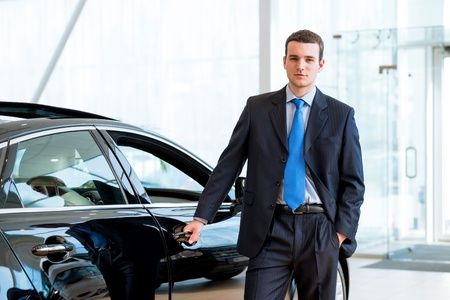 dealer stands near a new car in the showroom, put one hand on the car photo