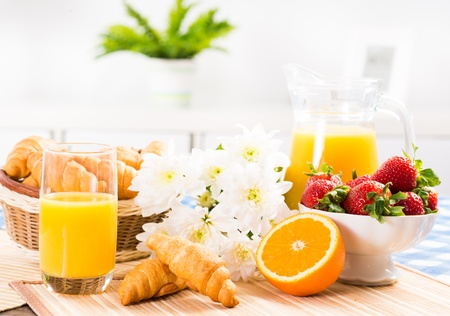 continental breakfast: orange juice, croissants and strawberries